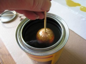 Dunk the egg into the can of varnish